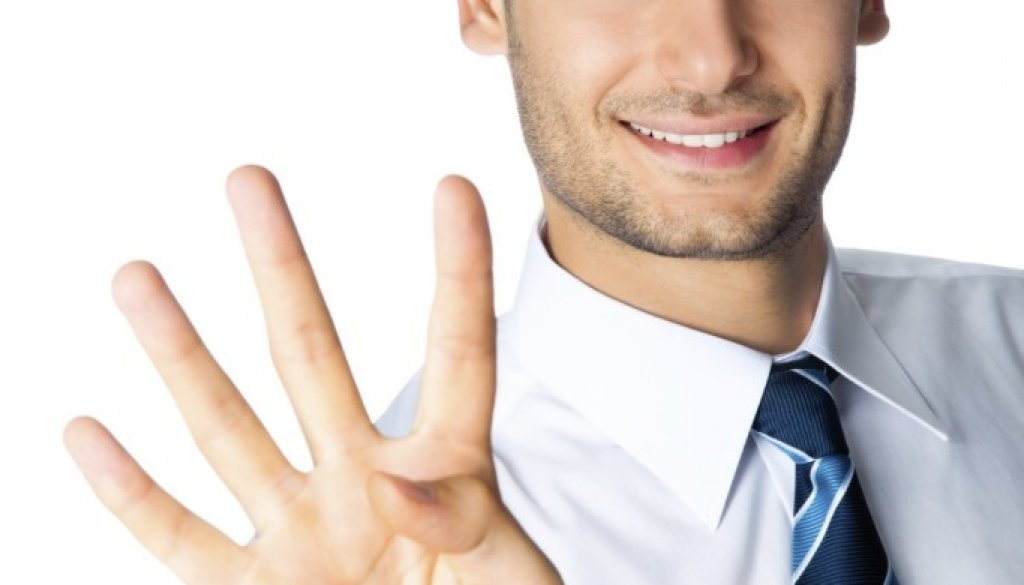 Happy businessman showing four fingers, isolated on white