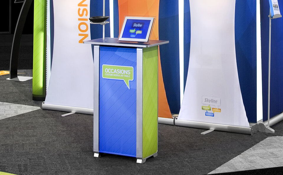 """Occasions® tables offer easy-to-install accessories including shelves for showcasing product; literature holder and digital screen mount for presentations. Built-in are two 9"""" x 14"""" inch shelves that provide concealed storage for easy access. A table fits into a soft-sided shipping case that has a handle and shoulder strap for easy transport."""