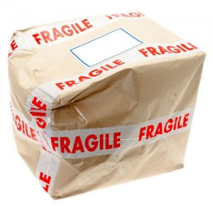 Damaged cardboard box that was covered with fragile tape - studio shot with a white background