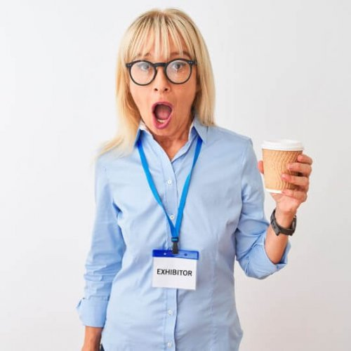 Woman with shocked expression holding a cup of coffee, Tradeshow solutions, Skyline Entourage
