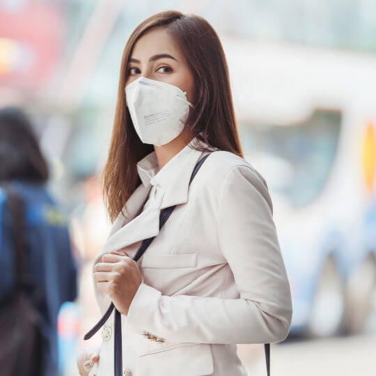 Woman wearing a face mask while travelling, Trade show solutions, Skyline Entourage