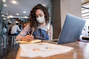 Woman working on laptop in a public space while wearing a face mask, PPE, Skyline Entourage, Safety Solutions
