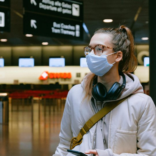 Young woman in airport wearing disposable face mask, Safety, Travel, Covid19, Coronavirus, Skyline Entourage