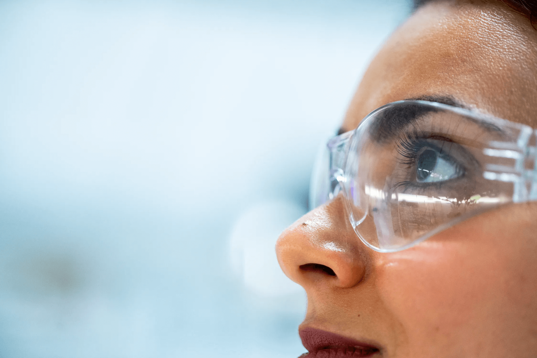 Close up side view of woman wearing safety glasses