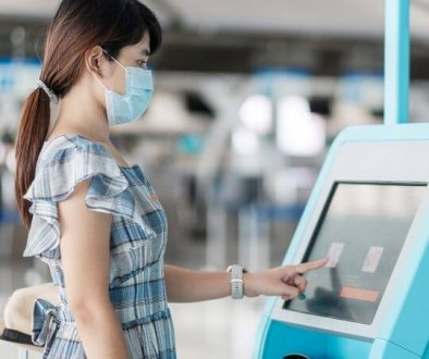A girl wearing a mask in front of a safety kiosk with a touch screen at a trade show, covid-19 solutions, events, Trade Show Technologies, skyline entourage