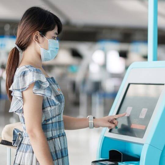 A girl wearing a mask in front of a safety kiosk with a touch screen at a trade show, covid-19 solutions, events, nouvelles technologies, skyline entourage