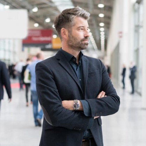 Man in a black suit standing in an exhibition hall, tradeshows, exhibiting, communication tips, skyline entourage